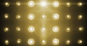 闪动的发光的金黄阶段轻型娱乐节目,在黑暗,在黑色的金温暖的柔光聚光灯罢工的聚光灯放映机 免版税库存照片