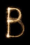 从闪烁发光物字母表的英国信件B在黑背景 免版税图库摄影