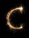 从闪烁发光物字母表的英国信件C在黑背景 库存照片
