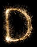 从闪烁发光物字母表的英国信件D在黑背景 库存图片