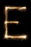 从闪烁发光物字母表的英国信件E在黑背景 库存照片