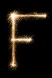 从闪烁发光物字母表的英国信件F在黑背景 库存照片