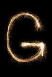 从闪烁发光物字母表的英国信件G在黑背景 库存照片