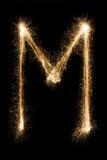 从闪烁发光物字母表的英国信件M在黑背景 免版税库存照片