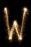 从闪烁发光物字母表的英国信件W在黑背景 免版税库存照片