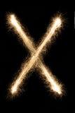从闪烁发光物字母表的英国信件x在黑背景 库存照片