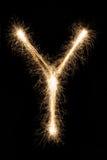 从闪烁发光物字母表的英国信件Y在黑背景 库存图片