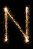 从闪烁发光物字母表的英国字母N在黑背景 免版税库存照片