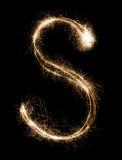 从闪烁发光物字母表的英国字母S在黑背景 图库摄影