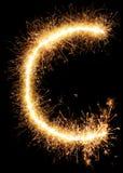 闪烁发光物烟花在黑色的光字母表C 库存照片