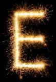 闪烁发光物烟花在黑色的光字母表E 免版税库存照片