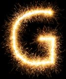 闪烁发光物烟花在黑色的光字母表G 免版税库存照片