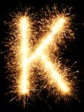 闪烁发光物烟花在黑色的光字母表K 免版税图库摄影