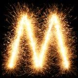 闪烁发光物烟花在黑色的光字母表M 库存图片