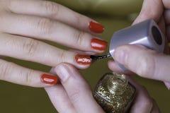 闪烁在金子在女性的红色钉子以后 免版税库存图片