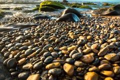 闪烁在阳光下的五颜六色的小卵石在一个多岩石的海滩 免版税库存照片