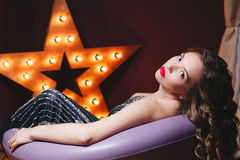 闪烁的年轻美丽的卷曲妇女穿戴与在黑暗的背景的红色嘴唇 Copyspace 概念庆祝 免版税库存图片
