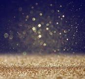 闪烁葡萄酒点燃背景 轻的金子和黑色 defocused 免版税库存照片