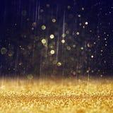 闪烁葡萄酒点燃背景 轻的金子和黑色 defocused 图库摄影