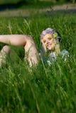 闪耀的帽子的年轻白肤金发的女孩在绿草说谎 免版税库存图片