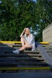 闪耀的帽子的年轻白肤金发的女孩坐台阶 免版税库存照片