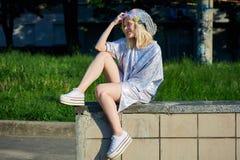 闪耀的帽子的年轻白肤金发的女孩坐边界 图库摄影