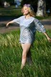 闪耀的帽子的年轻白肤金发的女孩走在绿草的 免版税图库摄影