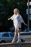 闪耀的帽子的年轻白肤金发的女孩走在街道上的 免版税库存图片