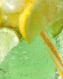 闪耀的新鲜的柠檬水特写镜头与冰的,切片石灰和柠檬,薄菏叶子与塑料秸杆的 大泡影 库存图片