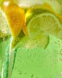 闪耀的新鲜的柠檬水特写镜头与冰的,切片石灰,柠檬和色的塑料秸杆在玻璃与大 库存照片