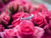 闪耀的金刚石定婚戒指在其中一朵小桃红色玫瑰中伟大为华伦泰 免版税库存图片