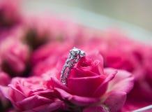 闪耀的金刚石定婚戒指在其中一朵小桃红色玫瑰中伟大为华伦泰 免版税库存照片