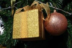 闪闪发光金黄当前垂悬在圣诞树的箱子和红色球 库存图片