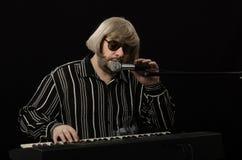 闭上他的眼睛的有胡子的音乐家,当唱歌时 免版税库存照片