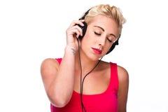 闭合的对妇女年轻人的眼睛听的音乐 免版税库存照片