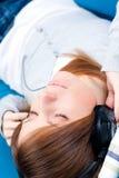 闭合的对年轻人的眼睛女孩听的音乐 免版税库存图片