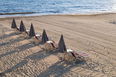 闭合的沙滩伞lougners、椅子和sunbeds线  库存图片