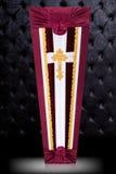 闭合的用在灰色豪华背景的布料盖的bordo和白色棺材 有金教会十字架的棺材 免版税库存照片
