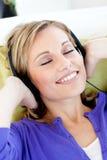 闭合的眼睛听放松的音乐妇女 库存图片