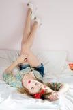 闭合的眼睛年轻美丽的白肤金发的女孩牛仔裤短缺说谎在后面白色床上的花衬衣高跟鞋把您的脚放在墙壁上 库存图片