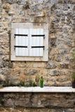 闭合的窗口在有一个绿色酒瓶的一个石墙关闭 免版税图库摄影