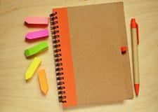 闭合的笔记本、笔和贴纸 免版税库存照片