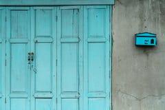 闭合的绿色或蓝色木门和空的邮箱在房子破裂的混凝土墙上  有破裂的水泥墙壁的老家 葡萄酒 免版税图库摄影