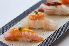 闭合的被火炬点燃的Salmoni寿司、Hotate扇贝寿司和被火炬点燃的Hamachi鲱的鱼寿司 库存图片