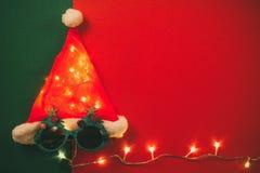 问候季节概念 有星光和glas的圣诞老人帽子 免版税图库摄影