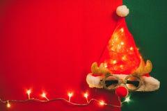 问候季节概念 有星光和glas的圣诞老人帽子 免版税库存照片