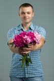 问候 给花的花束人 与花的年轻美好的被迷恋的人便装样式 免版税库存照片