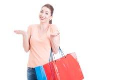 问和培养肩膀的妇女运载的购物袋 库存图片