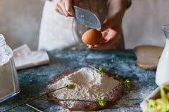 闯进与刀子的一个鸡蛋面粉小山  烹调烘烤 女性手面包师特写镜头 在裂化前 库存照片