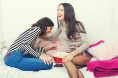 说闲话两个美丽的十几岁的女孩在家笑和 免版税库存图片